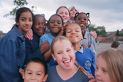 Multiracial group of primary school children standing together in playground smiling,
