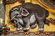 """An imagined elephant carving by an artist who had never seen one. Toshogu Shrine is the final resting place of Tokugawa Ieyasu, the founder of the Tokugawa Shogunate that ruled Japan for over 250 years until 1868. Ieyasu is enshrined at Toshogu as the deity Tosho Daigongen, """"Great Deity of the East Shining Light"""". Initially a relatively simple mausoleum, Toshogu was enlarged into the spectacular complex seen today by Ieyasu's grandson Iemitsu during the first half of the 1600s. The lavishly decorated shrine complex consists of more than a dozen buildings set in a beautiful forest. Countless wood carvings and large amounts of gold leaf were used to decorate the buildings in a way not seen elsewhere in Japan. Toshogu contains both Shinto and Buddhist elements, as was common until the Meiji Period when Shinto was deliberately separated from Buddhism. Toshogu is part of Shrines and Temples of Nikko UNESCO World Heritage site."""