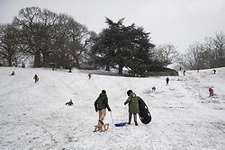 © Licensed to London News Pictures. 09/02/2021. London, UK. Members of the public sled in a snowy Greenwich park in South East London. Snow is expected for large parts of the UK and a yellow weather warning is in place in parts of England as Storm Darcy hits the UK. Photo credit: George Cracknell Wright/LNP