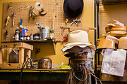 A straw hat on a block after steaming, with a tipper block pressing the center crease in place. On the left is a rack over a steam generator; hanging from the hat block are cords used to form the fold between the crown and the brim, as well as to shape the edge of the brim.
