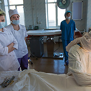 CAPTION: Fifth Year dental students from Volgograd State Medical University observe carefully as Dr Fomenko starts work, marking where she'll be making incisions. LOCATION: Volgograd City Hospital #1, Volgograd, Russia. INDIVIDUAL(S) PHOTOGRAPHED: Three Fifth Year dental students from Volgograd State Medical University (left), Ksenia Kalashnikova (behind, wearing light blue), Dr Irena Fomenko (surgeon), Lubov Kalganova (wearing dark blue) and Valentina Panteleeyeva (baby).