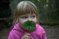 A 4 year old girl playing with a leaf in the rain forest.