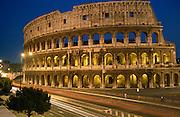 Traffic streaks past a floodlit Roman Colosseum on Via dei Fori Imperiali, Rome Italy