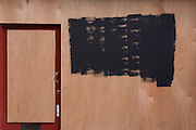An anonymous shop doorway and window has been boarded up with plyboard, identifying writing obscured with black paint in central London, a victim of the UK recession.