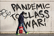 Fea0094740. Daily Telegraph <br /> <br /> DT News<br /> <br /> People on their way to work in SE London  passing a mural on the first day of an official lockdown in Britain's capital city .<br /> <br /> London  24 March 2020