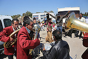 """A Balkan gypsy brass band play at a christening ceremony of Yardani's family, in the camping outside Saintes Maries de la Mer<br /><br />""""Le Pelerinage des Gitans""""; the French gypsy pilgrimage of Saintes Maries de la Mer, Camargue, France<br /><br />Sainte Sara is an uncannonized saint, who legend says looked after the Christian Saints Marie Jacobe and Marie Salome, cousins of Mary Magdalene, who arrived, it is said, on the shores of the Camargue in a rudderless boat. Saint Sara is the patron saint of gypsies who come from far and wide to see her. There are even paintings of Sara as 'Kali' the black saint in Eastern Europe. Sara may have been the priestess of 'Ra' the sun-god or even servant girl to the Christian saints. No-one really knows.<br /><br />For a few weeks of the year, Roma, Gitan and Manouche gypsies come from all over Europe in May, camping in caravans around Saintes Maries de la Mer. It is a festive time where they play music, dance, party and christen their children. They all go to see Saint Sara in the crypt, kissing or touching her forehead. Many put robes on her shoulders, making her fat for the procession. In the main Gypsy procession of the 24th May, Saint Sara is allowed to leave her crypt, beneath the church, and is carried from the church to the shores of the mediterranean and back again. One day a year she is free from her prison. Hundred's of years ago the Gypsies used not even to be allowed into the church, only into the crypt like Sara...<br /><br />Roma gypsies still suffer oppressive prejudice and racism and are one of the ethnic groups the most persecuted and marginalised across Europe. The festival is one of the times where they celebrate with people of all races, their faith and traditions"""
