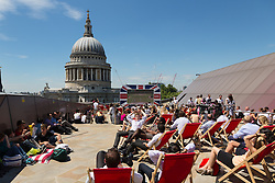 © Licensed to London News Pictures. 03/04/2014. London, UK. Crowds of office workers and tourists watch Wimbledon tennis on a large screen in the sunshine near St Paul's Cathedral in London at lunchtime on 3 July 2014. Photo credit : Vickie Flores/LNP