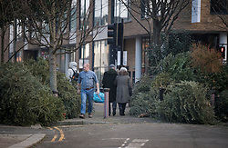 © Licensed to London News Pictures. 07/01/2021. London, UK. Members of the public walk between piles of Christmas tress at a recycling point in Kensal Green, West London, which haven't been collected during a third national Lockdown. Photo credit: Ben Cawthra/LNP
