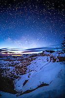 Just before the sun rises, the remnants of the Milky Way and brightly shining stars illuminate the snowing canyon hoodoos of Bryce Canyon National Park in Winter.