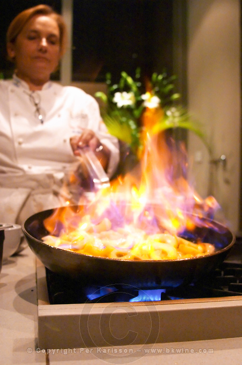 Dolly Irigoyen frying slices of apples in a frying pan, flaming the apples with branding making a big flame fire in the pan. The Dolly Irigoyen - famous chef and TV presenter - private restaurant, Buenos Aires Argentina, South America Espacio Dolli