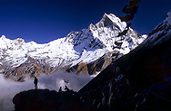 A man in the distance is watching the panorama from the Annapurna base camp at  4,130mt, in the north central Himalayas of Nepal. Furthest in the background and marked with snow is the Machapuchare mountain, sacred to the God Shiva and therefore off limits to climbing. <br /> Photo by Lorenz Berna