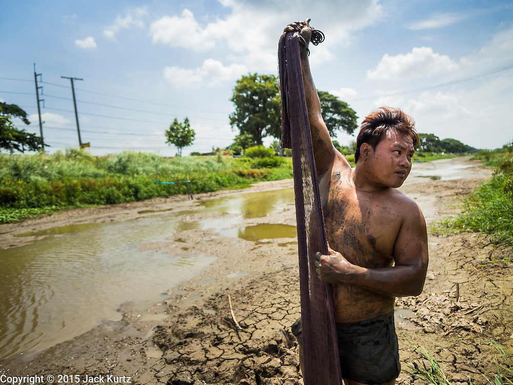 14 JULY 2015 - THAILAND:  A laborer goes net fishing in a khlong (irrigation canal) in Pathum Thani province. The canal, which is normally about 10 meters deep, is essentially empty. The drought that has crippled agriculture in central Thailand is now impacting residential areas near Bangkok. The Thai government is reporting that more than 250,000 homes in the provinces surrounding Bangkok have had their domestic water cut because the canals that supply water to local treatment plants were too low to feed the plants. Local government agencies and the Thai army are trucking water to impacted communities and homes. Roads in the area have started collapsing because of subsidence caused by the retreating waters. Central Thailand is contending with drought. By one estimate, about 80 percent of Thailand's agricultural land is in drought like conditions and farmers have been told to stop planting new acreage of rice, the area's principal cash crop.      PHOTO BY JACK KURTZ