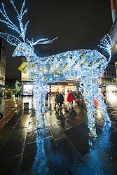 Glasgow, Scotland, UK. 20 November 2020. On evening shortly before the severest level 4 lockdown will be imposed at 6pm, shoppers are out on the streets of Glasgow doing last minute Christmas shopping before the shops close for 3 weeks. Views in evening as shops and businesses are closing. Pictured;  Reindeer on Argyle Street. .Iain Masterton/Alamy Live News