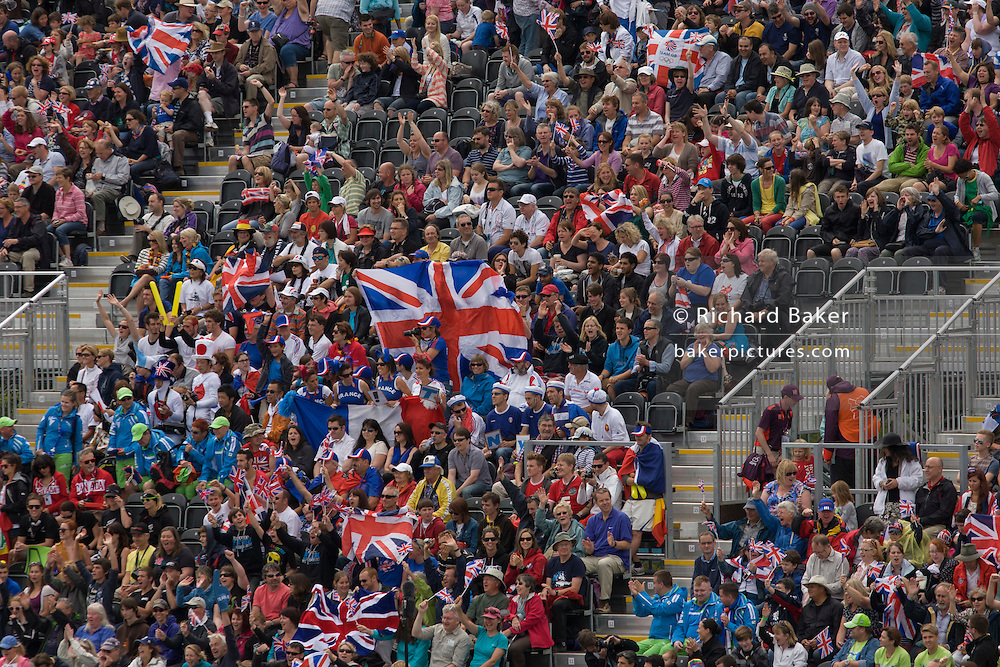 British fans hold up Union Jack flags surrounded by crowds of sports supporters seem en mass during the canoe slalom heats at the Lee Valley White Water Centre, north east London, on day 3 of the London 2012 Olympic Games.