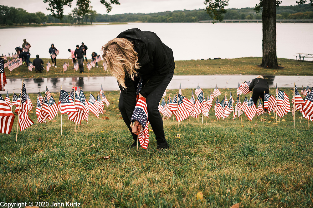 10 SEPTEMBER 2020 - DES MOINES, IOWA: CARILYN BETTIS, from Urbandale, sets out American flags along Gray's Lake. About 25 volunteers braved cold and rainy weather Thursday to line the west end of Gray's Lake in Des Moines with American flags. The display of flags was a part of an annual event called the 9/11 Tribute Trail. About 3,000 flags were set out in memorial of the 3,000 people killed in the 9/11 terrorist attacks.     PHOTO BY JACK KURTZ