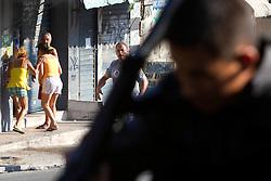 Moradores tentam ajudar um homem que asfixiou-se quando seu bar pegou fogo na favela do Morro do Alemão, em 27 novembro de 2010 no Rio de Janeiro, Brasil. Centenas de soldados e policiais se juntaram para uma repressão sobre as gangues de drogas. No início desta semana, a polícia forçou os membros das gangues saírem da favela Vila Cruzeiro, com o auxílio de tanques M113 transportadores blindados de pessoal. FOTO: Jefferson Bernardes/Preview.com