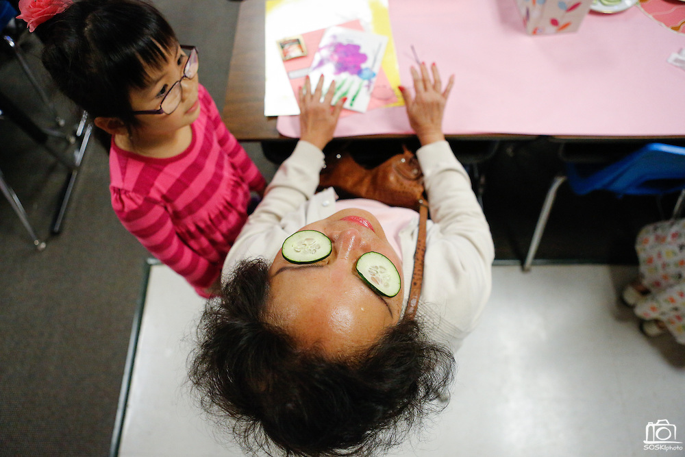 Jannet Nguyen, 7, watches as her grandmother, Vo Kim, lays back with cucumbers over her eyes during the 1st grade Mother's Day Spa Day at Sinnott Elementary School in Milpitas, California, on May 10, 2013. (Stan Olszewski/SOSKIphoto)