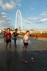 Kids splashing in puddle near pink flip flops on Continental Avenue Bridge with Margaret Hunt Hill Bridge in background, Trinity River, Dallas, Texas, USA.