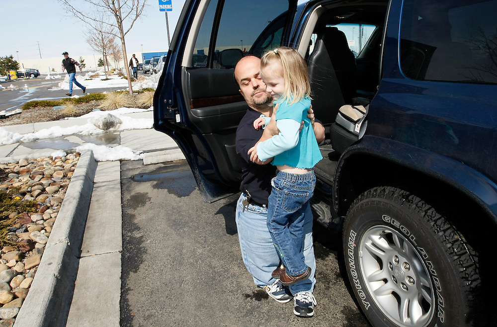 Chris Kotzian (L) lifts he daughter Avery, 4 out of his car for a shopping trip in Thornton, Colorado March 25, 2010.  Chris is a achondroplasia dwarf while Avery, 4 is average sized. Preferring to be called little persons Chris is active in the Little People of America, the only dwarfism support organization that includes all 200+ forms of dwarfism.  REUTERS/Rick Wilking (UNITED STATES)