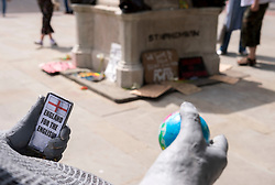 "© Licensed to London News Pictures; 15/06/2020; Bristol, UK. A new mystery statue of a caricature Englishman has been placed by the now empty Colston plinth seen in the background on the Monday morning after an ""All Lives Matter"" protest at the weekend to ""defend the Cenotaph"". The grey statue shows a bald man resting in a wheelie bin with the words ""Spoiler: St George was Turkish"" on the front. He is holding a small globe in one hand and a mobile phone in the other hand with a screen showing the St George flag and words ""England for the English"". The character wears a string vest over a beer belly and looks over to where Colston's statue was torn down from its plinth a week ago. The artist is not known but the statue looks similar to ""Ruth"", a character who appeared on Victoria Street in April 2018. This comes just over a week after the statue of Edward Colston which has stood in Bristol city centre for over 100 years was pulled down by protestors and thrown in Bristol Docks during a Black Lives Matters rally and march through the city centre. The rally was held in memory of George Floyd, a black man who was killed on May 25, 2020 in Minneapolis in the US by a white police officer kneeling on his neck for nearly 9 minutes. The killing of George Floyd has seen widespread protests in the US, the UK and other countries against both modern day racism and historical legacies of slavery. Edward Colston (1636 – 1721) was a wealthy Bristol-born English merchant involved in the slave trade, a Member of Parliament and a philanthropist. He supported and endowed schools, almshouses, hospitals and churches in Bristol, London and elsewhere, and his name is commemorated in several Bristol landmarks, streets, three schools and the Colston bun. Photo credit: Simon Chapman/LNP."
