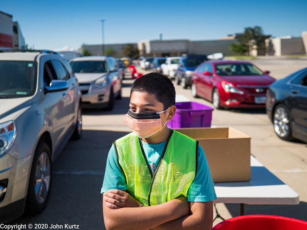 29 MAY 2020 - DES MOINES, IOWA: BRIAN MORALES, 13, a volunteer, waits for a produce distribution to start in a mall parking lot in Des Moines. The Des Moines Area Religious Council (DMARC) and Capitol City Fruit from Norwalk, IA, gave away 1,800 boxes of fresh produce with a mix of vegetables and fruit. The boxes contain enough produce to feed a family of four for a week. The produce was provided by the USDA Farmers to a Families food program. Because of the COVID-19 pandemic, the unemployment rate in Iowa hit 10.2% in May, the highest unemployment rate ever recorded in Iowa and food insecurity in Iowa is impacting communities throughout the state.         PHOTO BY JACK KURTZ