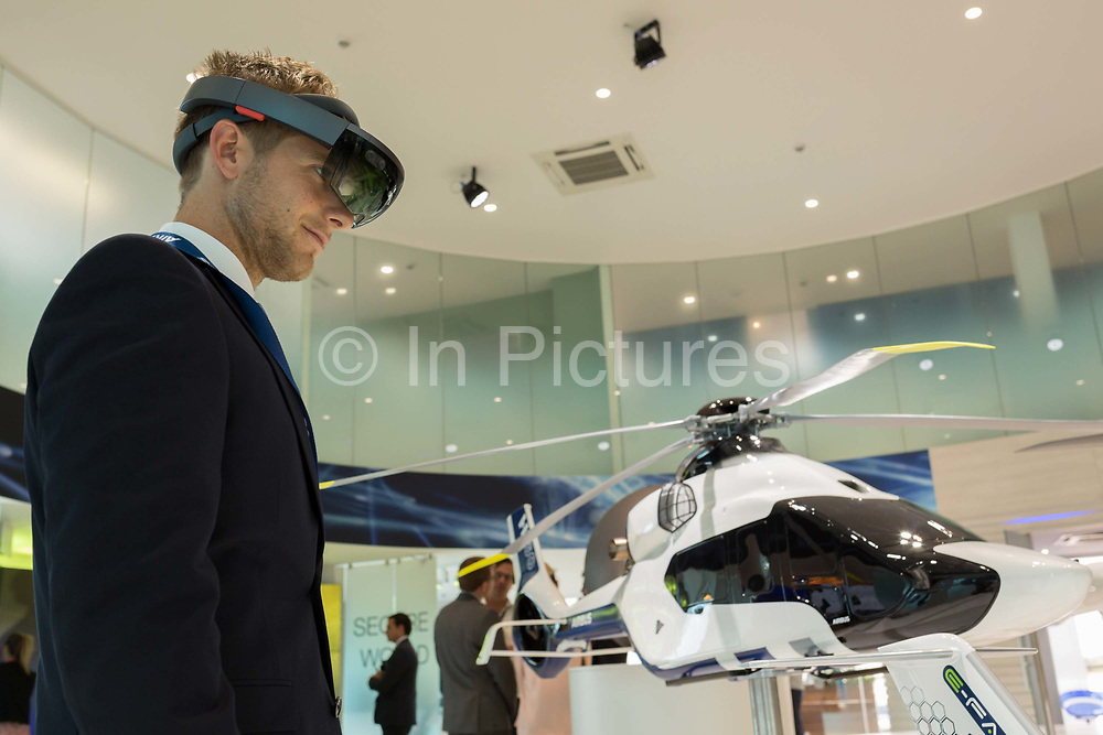 A visitor looks at an interactive augmented reality scale model of the Airbus H160 helicopter in the companys hospitality chalet at the Farnborough Airshow, on 18th July 2018, in Farnborough, England. The Airbus Helicopters H160 formerly X4 is a medium utility helicopter being developed by Airbus Helicopters.