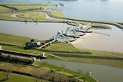 Nederland, Gelderland, Maurik, 11-02-2008; stuw in de rivier de Neder-Rijn, dient om waterpeil in de rivier te reguleren; de vizierschuif van de stuw is gesloten, hierdoor is er verschil in waterhoogte, dit verval wordt gebruikt om een waterkrachtturbine aan te drijven - de waterkrachtcentrale is het lage gebouw achter de stuw; de meanderende waterloop - met bocht, boven de stuw, is een vistrap (of vispassage) waardoor vissen de gesloten stuw stroomopwaarts kunnen passeren; de recreatieplas die hoort bij het Eiland van Maurik boven in beeld; flood barrier in the Lower Rhine River regulates water level; barrier is closed, there is a difference in water height, this decline is used for a hydro turbine - the hydroelectric poer station is the low building behind the dam, the meandering waterway - abov the barrier is a fish staircase or  fish ladder trapwich enables fish to pass the barrier; .neder rijn, watersport, Lower Rhine, watersports.luchtfoto (toeslag); aerial photo (additional fee required); .foto Siebe Swart / photo Siebe Swart