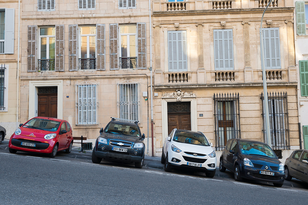 A variety of cars made by Citroën, Chevrolet, Hyundai, Renault parked on a sloping street outside apartments in Marseille, France