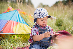 Little boy with cherry sitting on picnic blanket in the countryside, Bavaria, Germany