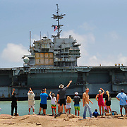 Spectators wave as the USS Independence is towed past them into the Brownsville Ship Channel for salvage operations Thursday June 1, 2017 on South Padre Island. The Independence served in the U.S. Navy from 1959-1998. Nathan Lambrecht/The Monitor