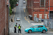 """Oldham, United Kingdom, June 21, 2021: Police cordoned the Greenacres Road in Oldham as local communities along with their men, women and children are gathered to protest outside """"CAIRO House"""" on Monday, June 21, 2021. Following the arrest of Palestine Action activists who scaled the roof of """"Cairo House"""" on Monday morning, people are demanding an immediate shutdown of Elbit subsidiaries in Britain. This is the ongoing protest forms of the human rights activists group in the UK targeting Israeli owned weapons manufacturer Elbit Systems. Activists argue that arms being manufactured in the facility are being used in indiscriminate attacks against the Gaza Strip. (VX Photo/ Vudi Xhymshiti)"""