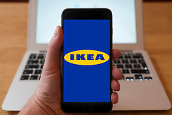 Using iPhone smartphone to display logo of IKEA the home furnishing superstore