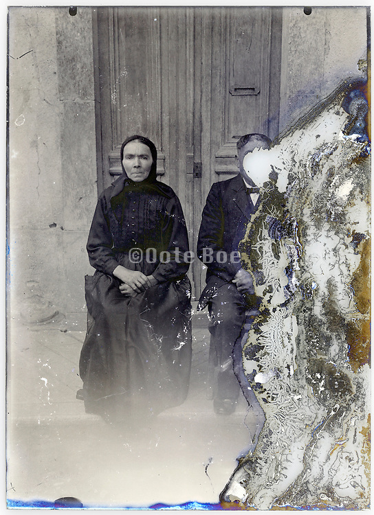 senior couple posing in front of door early 1900s severely eroded glass plate
