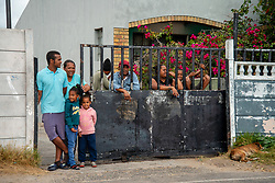 Parkwood, Cape Town, South Africa: A family looks out of their gate, as community health workers are doing door-to-door COVID-19 screenings in Parkwood, a suburb of Cape Town on the Cape Flats, on Thursday, April 16, 2020. The Western Cape government is ramping up mass screening and testing to stop the spread in vulnerable communities, such as low-income areas where many are living in multi-family households in crowded spaces. The aim is early detection, so that those who are testing positive can be removed to quarantine elsewhere. PHOTO: EVA-LOTTA JANSSON