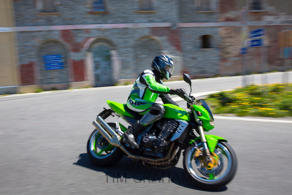 Motorcyclist on Kawasaki motorbike drives The Stelvio Pass, Passo dello Stelvio, Stilfser Joch, to Bormio, Italy