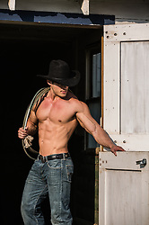 shirtless muscular cowboy in a barn doorway on a ranch