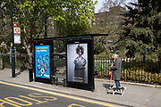 Woman with a shaggy haired dog waits at a bus stop which is advertising an estate agent depicting a woman with bedraggled hair in the upmarket area of Chelsea on 14th April 2021 in London, United Kingdom. Chelsea is one of the principal areas for exclusive, luxury goods in West London. It is known as a district where the rich and wealthy shop, mostly for high end fashion and jewellery.