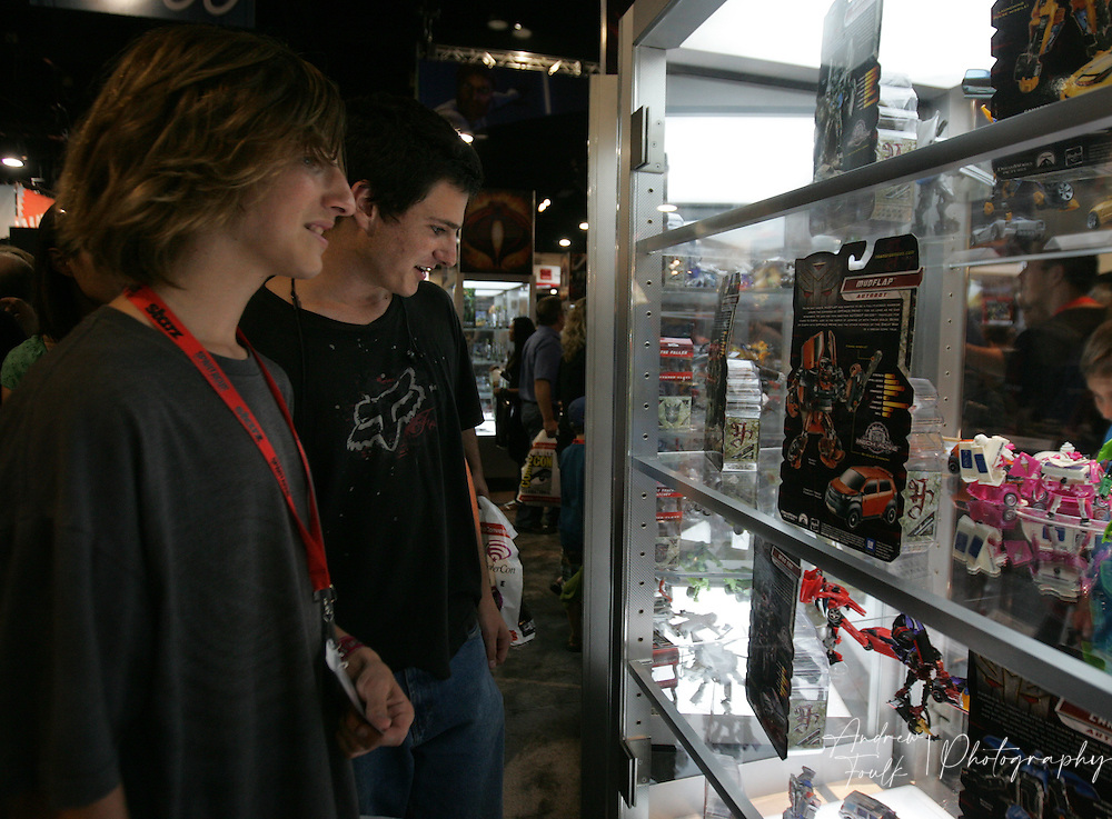 """/Andrew Foulk/ For The North County Times/.Chad Seligman,15, and Zachary Wright, 17, both from Coronado, look at the """"Transformers"""" action figures, as they tour the floor, during preview night at the 40th annual San Diego Comic Con International."""