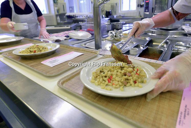 Nederland, Millingen aaan de Rijn, 20-10-2012 In een verzorgingshuis worden de warme maaltijden apart opgeschept en samengesteld. Instelling voor ouderen, voeding, eten, keuken, kok, kwaliteit voedsel. Ook oudere buurtbewoners komen hier eten. Foto: Flip Franssen/Hollandse Hoogte