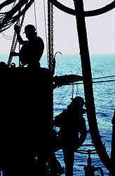 Silhouetted offshore oil rig workers with the ocean in the background.