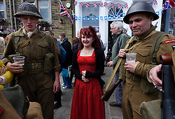 © Paul Thompson licensed to London News Pictures. 16/05/2015. Haworth, West Yorkshire, UK. A woman in a red dress chatting to soldiers during Haworth 1940s weekend, an annual event in which people dress in period costume and visit the village of Haworth to relive the 1940s.  Photo credit : Paul Thompson/LNP