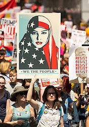 © Licensed to London News Pictures . 13/07/2018. London, UK. Placard featuring graphic of a woman wearing an American flag as a hijab . Demonstrators march from Portland Place to Trafalgar Square in protest against US President Donald Trump's UK visit . Photo credit: Joel Goodman/LNP