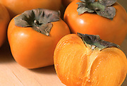 Close up selective focus photograph of a group of Fuyu Persimmons with a cut opened section of one