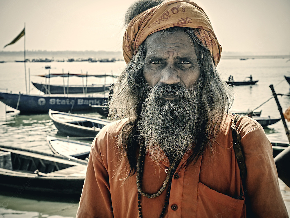 Man in sadhu clothes in Varanasi India. Sadhus are ascetics dedicated to achieving Moksha, liberation of the reincarnation cycle, through meditation and contemplation of Brahman. Many people in the city dress like sadhus only to receive money from the pilgrims that visit the city.