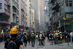 Hong Kong. 1 October 2019. After a peaceful march through Hong Kong Island by an estimated 100,000 pro democracy supporters, violent flared up at Tamar, Admiralty and moved through Wanchai district. Police used teargas and baton rounds and water cannon. Hard core group lit fires, threw bricks and Molotov cocktails at police. Violence continues into evening. Protestors retreat through Wanchai district. Iain Masterton/Alamy Live News.