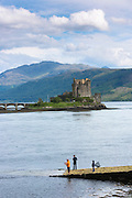 Fishermen fishing by Eilean Donan Castle, a highland fortress, in Loch Alshe at Dornie, Kyle of Lochalse in the western hIghlands of Scotland