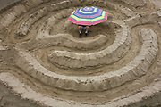 A young man sits on a sandbank beneath a sun brolley. With legs and feet protruding the man is in the middle of a sand maze constructed for the London Thames Festival, the annual celebration of all things related to London life and culture. The maze has been trodden by pairs of feet to create concentric circles that ultimately lead to the centre. Seen only at low-tide on the river's foreshore near Gabriel's Wharf, the stretch of fine, natural sandy beach is used by Londoners to sample a touch of seaside on fine summer days and was popular with Victorians before the arrivals of railways taking them to the coast. Nowadays the Thames is much cleaner after more stringent environment policies and the sand in some places is pure.
