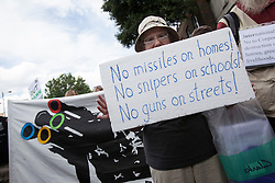 © licensed to London News Pictures. London, UK 28/07/2012. A protester posing with a placard against the defence precautions as anti-Olympics protesters marching from Mile End Park to Victoria Park in order to protest against the greed of the Olympic sponsors. Photo credit: Tolga Akmen/LNP