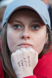© Licensed to London News Pictures. 23/03/2017. London, UK. A woman with the words 'We Are Not Afraid' written on her hand joins thousands at a vigil in Trafalgar Square for the victims of the Westminster terrorist attack, which took place on 22 March 2017. Photo credit: Rob Pinney/LNP