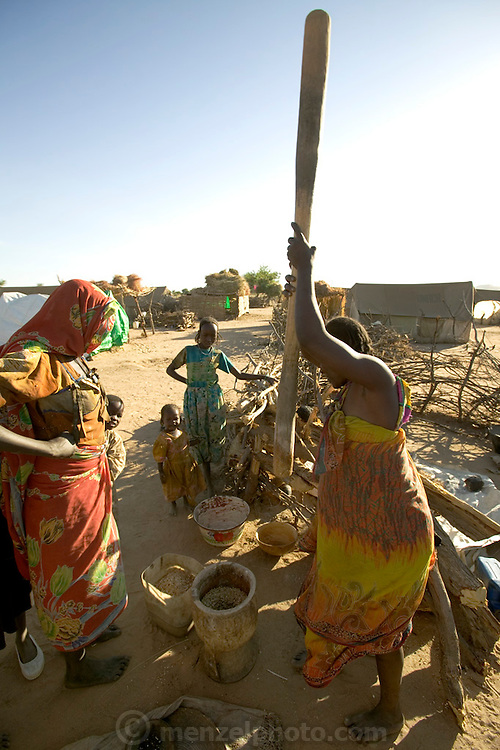 The Breidjing Refugee Camp, Eastern Chad on the Sudanese border shelters 30,000 people who have fled their homes in Darfur, Sudan. Food is distributed free of charge by the United Nations WFP (World Food Program). Here, women pound grain into meal with a traditional heavy wooden mortar and pestle. (Supporting image from the project Hungry Planet: What the World Eats.)